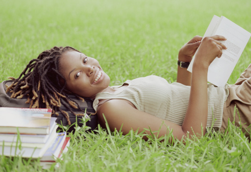 Young woman lying on grass, reading book, portrait, side view