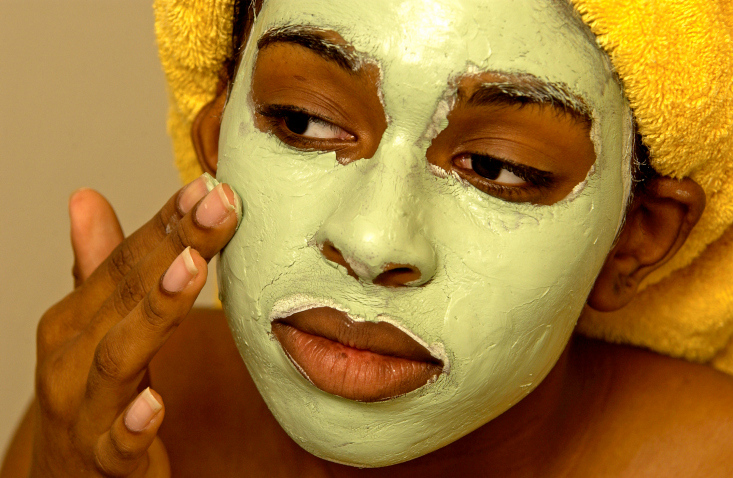 Woman putting on a facial mask