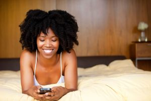 A black woman lying in bed using a cell phone. --- Image by © Michael Poehlman/Corbis