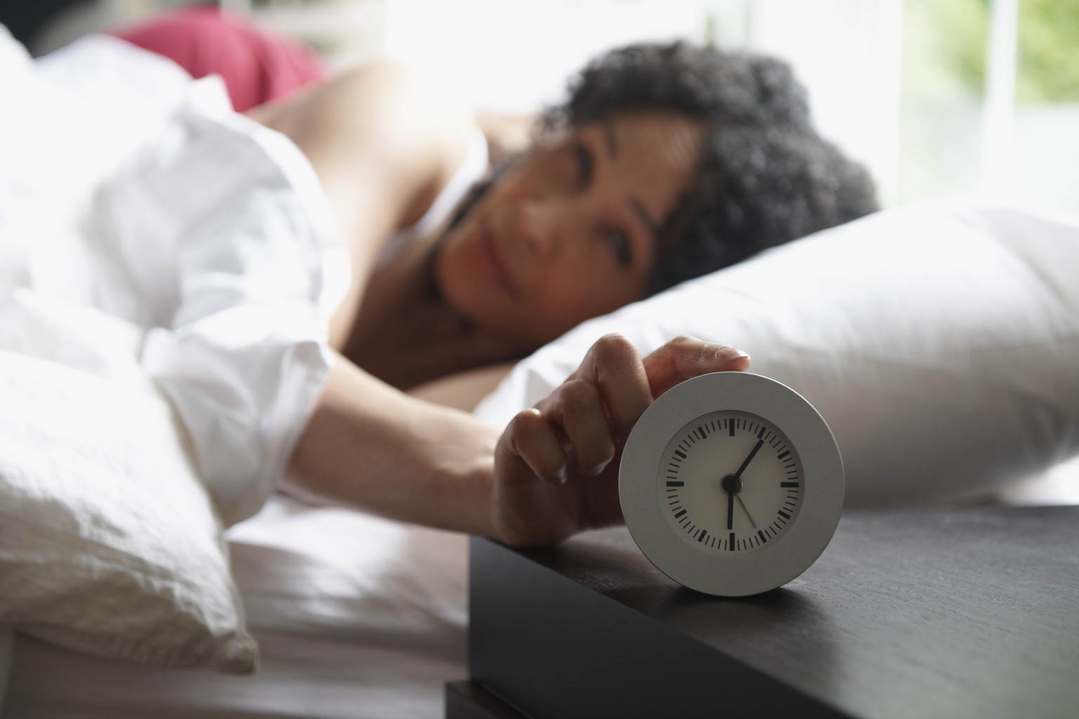 Black woman turning of alarm clock