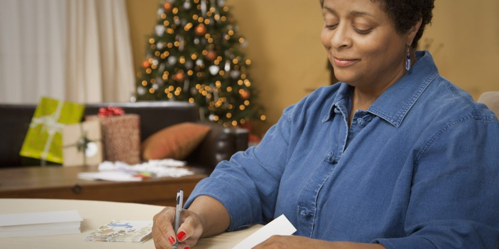 African woman writing Christmas cards