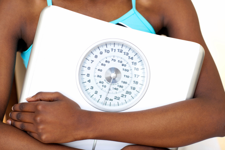 Close-up of a fitness woman with thumb up holding a weight scale