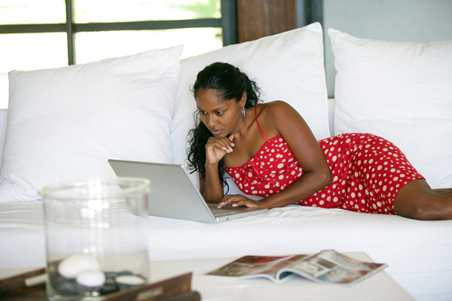 beautiful Afro-American woman lying on her bed with her laptop