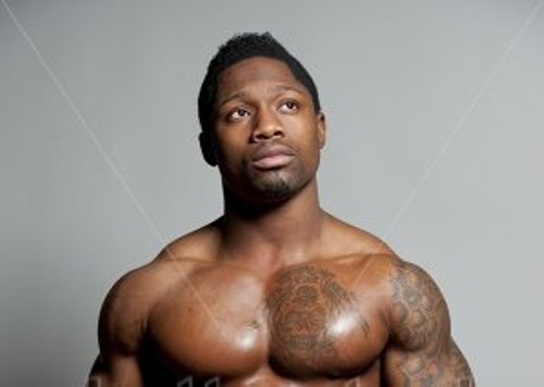 stock-photo-african-american-male-body-builder-posing-on-a-gray-background-while-looking-up-and-wearing-black-188246024