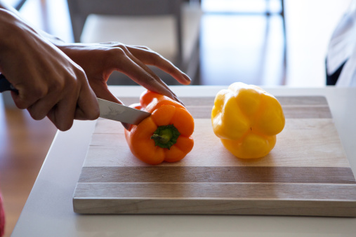 Young woman chopping orange pepper