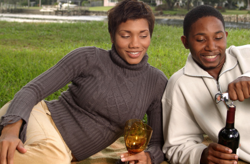 Young man and woman opening bottle of wine in park, smiling