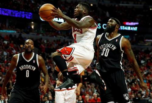 Chicago Bulls' Nate Robinson (C) goes to the basket between Brooklyn Nets' Andray Blatche (L) and Nets' Reggie Evans during the second half of Game 4 of their NBA Eastern Conference quarter-finals basketball playoff series in Chicago, Illinois, April 27, 2013. REUTERS/Jim Young (UNITED STATES - Tags: SPORT BASKETBALL)