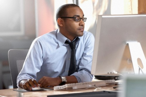 Dallas, Texas, USA --- African American businessman working at desk --- Image by © DreamPictures/Blend Images/Corbis