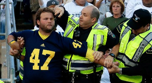 A Michigan fan is subdued by Police at Beaver Stadium during the second quarter an NCAA college football game between Penn State and Michigan in State College, Pa., Saturday, Oct. 12, 2013. Penn State won 43-40 in four over-time periods. (AP Photo/Gene J. Puskar)