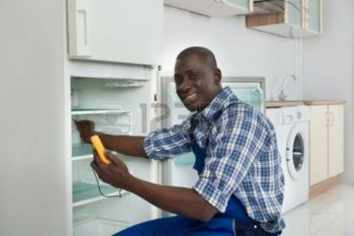 41933833-happy-african-technician-repairing-refrigerator-appliance-in-kitchen-room