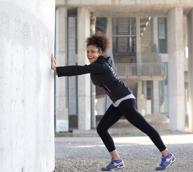 Smiling young sports woman stretching exercise outdoors