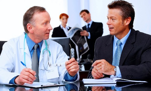 two business men a business woman and a doctor working and talking in modern office