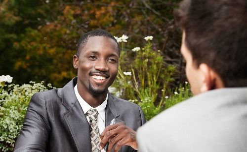 African American Businessman in Suit shaking hands with client. He has a wide, successful smile and strong, positive attitude.