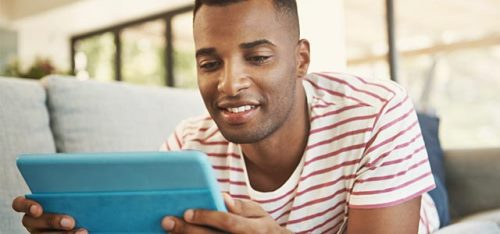black_man_looking_tablet_lying_down_sofa