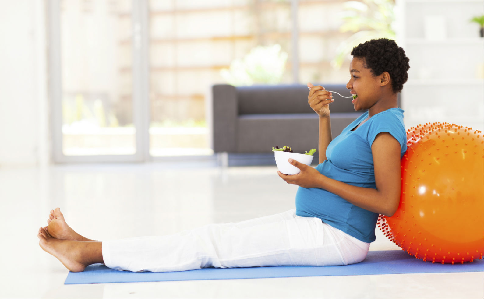 pregnant-african-american-woman-eating-healthy-salad-on-exercise-mat-FINAL