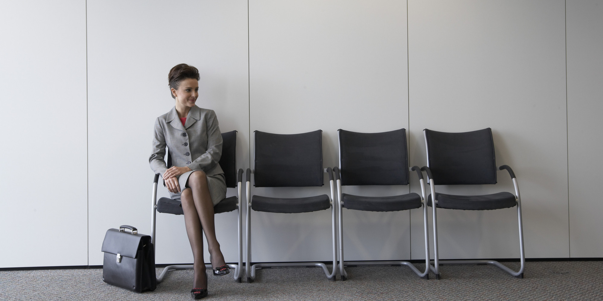 Businesswoman seated indoors, by briefcase, smiling