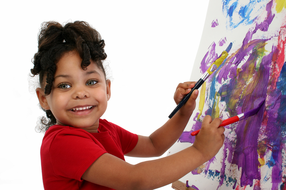Five-year-old African-American girl painting.