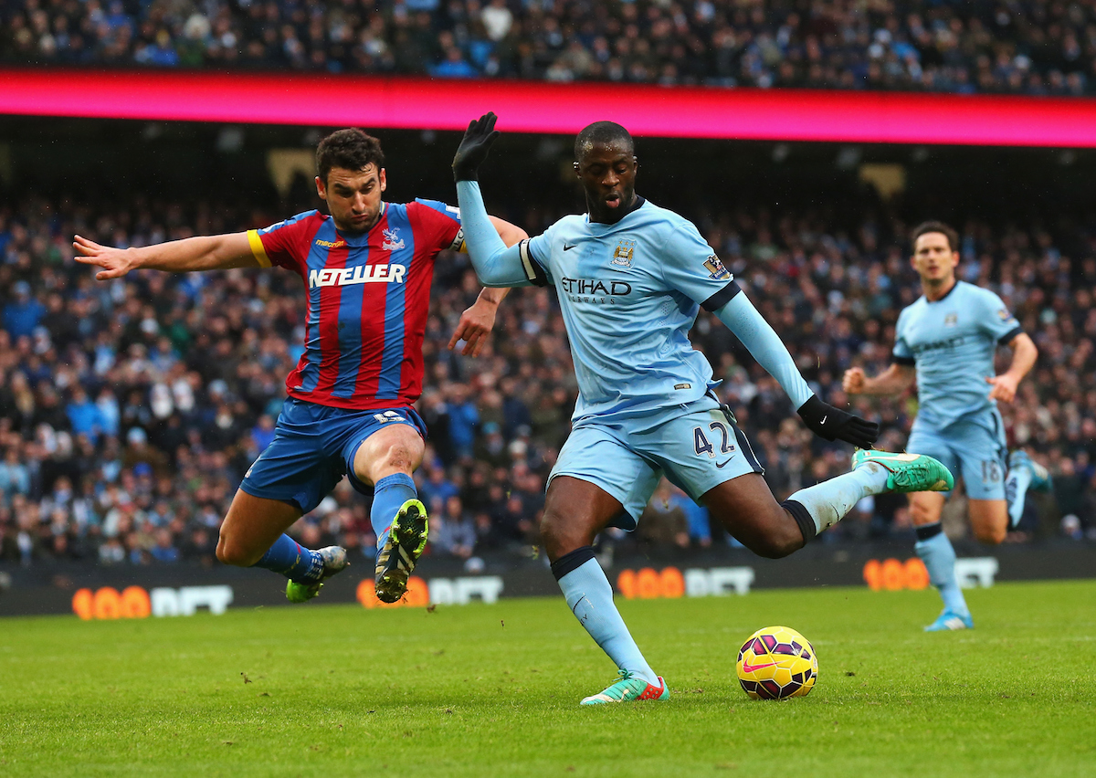 MANCHESTER, ENGLAND - DECEMBER 20: Yaya Toure of Manchester City scores his goal challenged by Mile Jedinak of Crystal Palace during the Barclays Premier League match between Manchester City and Crystal Palace at Etihad Stadium on December 20, 2014 in Manchester, England. (Photo by Alex Livesey/Getty Images)